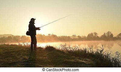 Silhouette of Fisherman at sunrise. Fisherman On Morning...