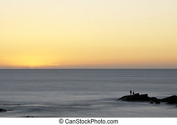 Silhouette of fisherman fishing at sunset at the ocean