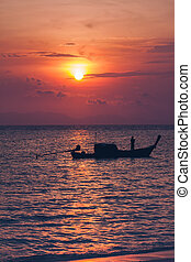 Silhouette of fisherman on boat in the sea with sunrise over horizon behind