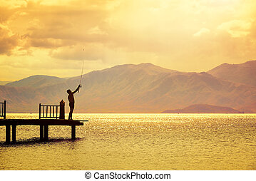 Silhouette of fisherman on pier on the background of beautiful mountains