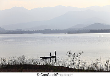 silhouette of fisherman on wood boat at lake.