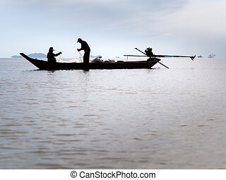 silhouette of fisherman prepare the net on long tail boat