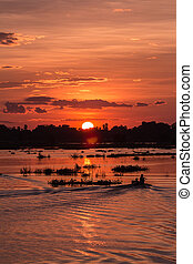Silhouette of fisherman to drive a boat on the lake at sunset scene in Mandalay, Myanmar