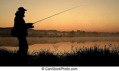 Silhouette of Fisherman at sunrise. Fisherman On Morning...