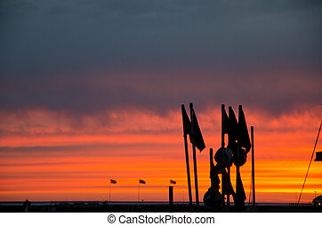 Silhouette of fishermans flags in sunset