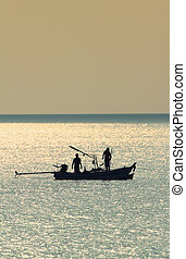 Silhouette of fishermen and boat at sunrise in vintage style