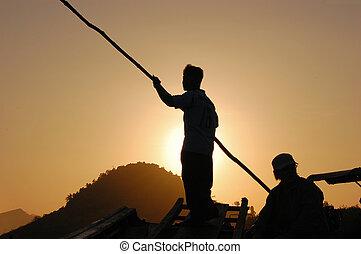 Silhouette of fishermen at sunrise