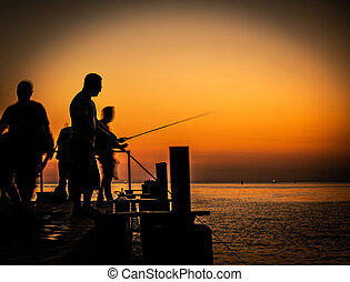 silhouette of fishermen at sunset