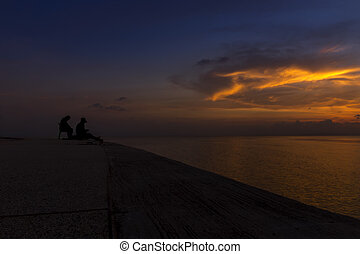 silhouette of fishermen at the lake with twilight sky.