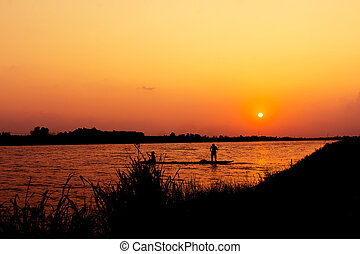 silhouette of fishermen catch fish in the canal sunset background