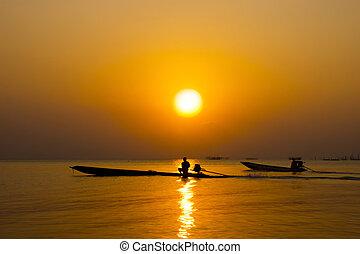silhouette of fishermen in a boat.