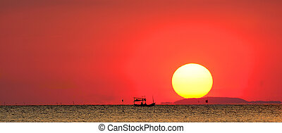 Silhouette of fishing boat in the sea with the sunset background