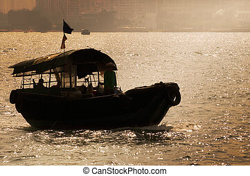 Silhouette of fishing boat with dramatic sunset light