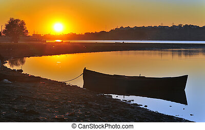 fishing boat with sunrise in the background