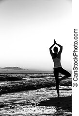 Silhouette of fit woman in sport clothes on seacoast doing yoga