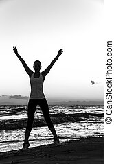 Silhouette of fit woman in sports gear on beach rejoicing