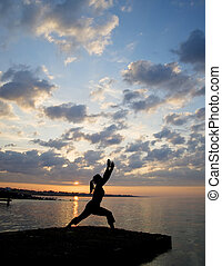 Silhouette of fit young woman doing stretching exercises on pier at sunrise