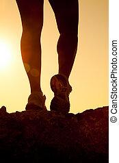silhouette of fitness girl legs running at sunset
