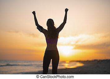 Silhouette of fitness young woman rejoicing on beach at dusk