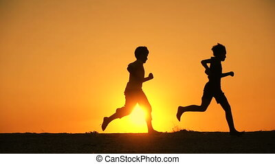 silhouette of five kids family runniing at sunset