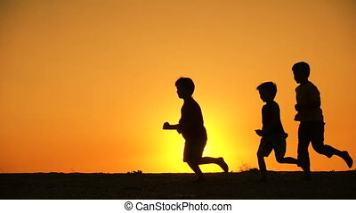 silhouette of five kids family running together at sunset, slow motion