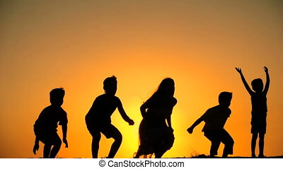 silhouette of five kids jumping together at sunset