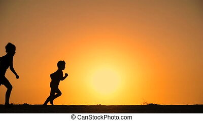 silhouette of five kids running at hill with sunset