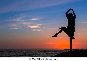 Silhouette of flexible girl on sea coast during sunset.