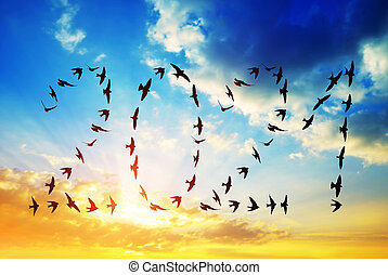 Silhouette of flock birds flying in 2021 formation into the New Year.