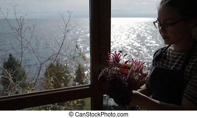 Silhouette of florist woman with bouquet at window with sea view.