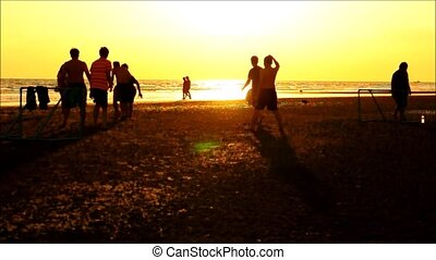 silhouette of football players on the beach at sunset