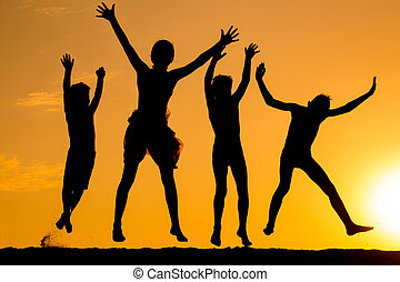 silhouette of four jumping kids against sunset