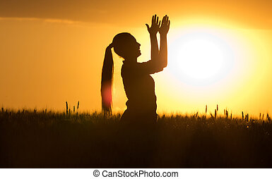 Silhouette of girl clapping hands at sunset
