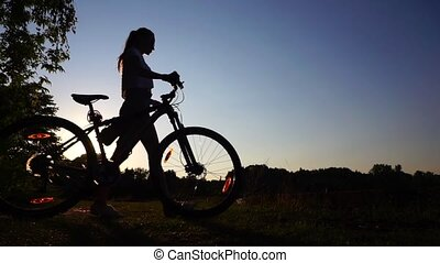 Silhouette of girl cyclist with ponytail hairstyle walking...