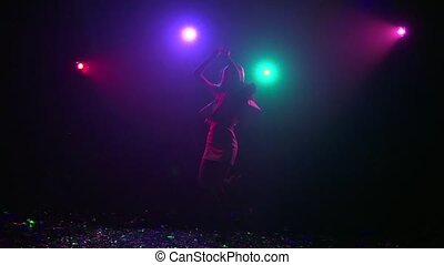 Silhouette of girl dancing with disco style lights. Slow motion