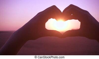 Silhouette of girl hands making heart symbol at sunrise