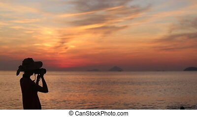 silhouette of girl in hat taking pictures of  sunrise above sea