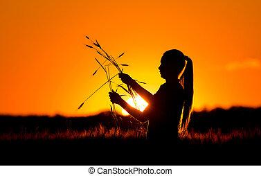 Silhouette of girl in wheat field