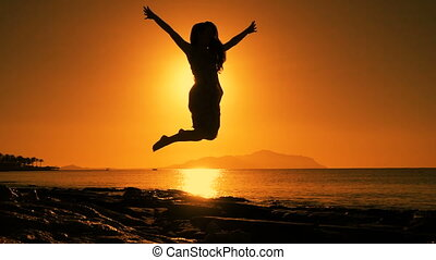 silhouette of girl jumping at sunrise