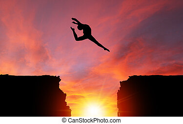 Silhouette of Girl Leaping Over Cliffs With Sunset Landscape