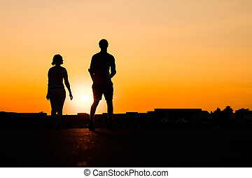silhouette of  girl looking up to boy on sunset sky background