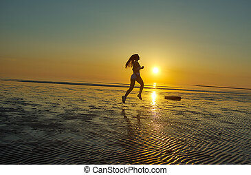 girl running by the sea on the beach