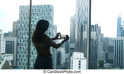 Silhouette of girl tourist standing at the window and taking photo on a mobile phone view of a skyscraper height in Kuala Lumpur. Malaysia.