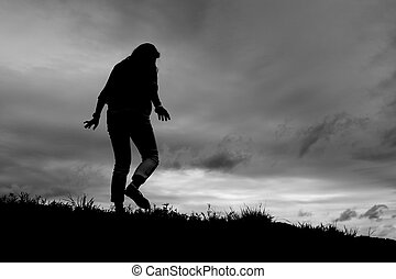 Silhouette of girl walking away on a grassy hill slope.