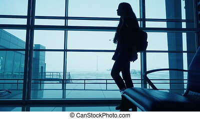 Silhouette of young girl walking on window of airport terminal with small backpack, slow motion