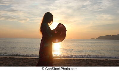 silhouette of girl who admires scenery of sunrise above sea