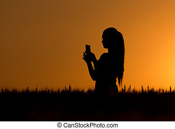 Silhouette of girl with cell phone
