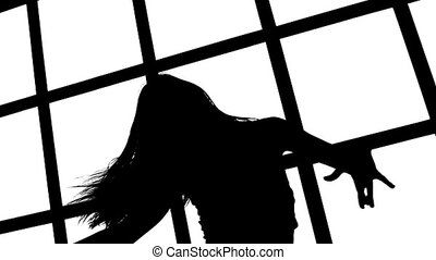 Silhouette of girl with long waving hair in profil on white background with grid window. Slow motion.