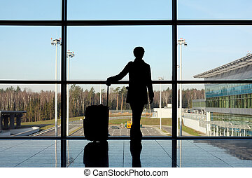 silhouette of girl with luggage standing near window in airport