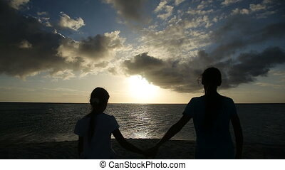 silhouette of girls on the beach at sunset